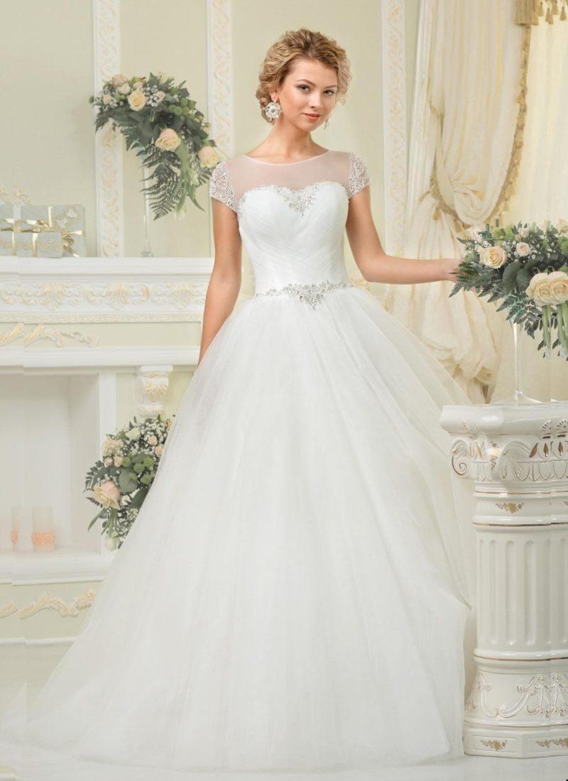 Пышное свадебное платье с полупрозрачной отделкой лифа и короткими рукавами.