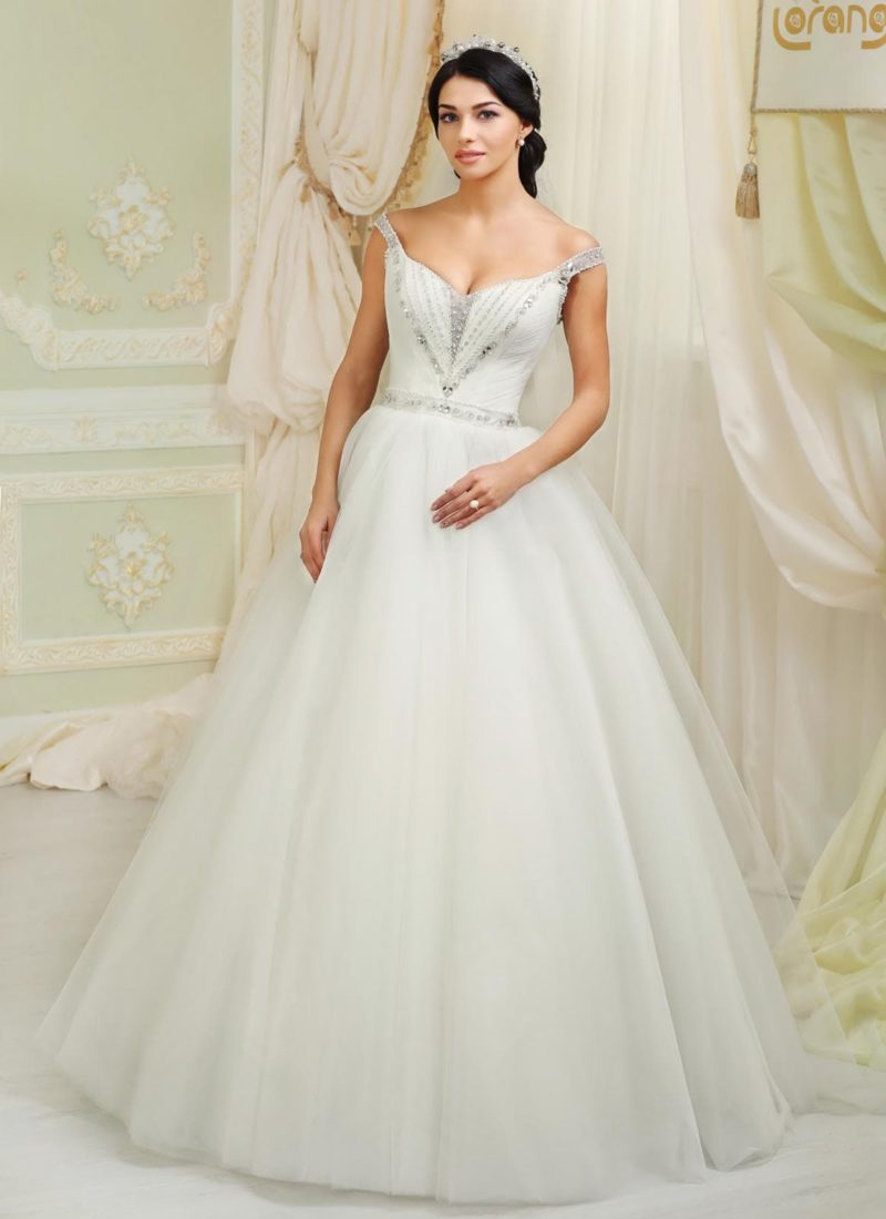 Открытое свадебное платье пышного силуэта с бретелями на предплечьях и сверкающей вышивкой.