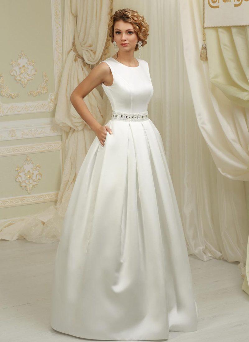 Атласное свадебное платье силуэта «принцесса» со сверкающим поясом и скрытыми карманами.