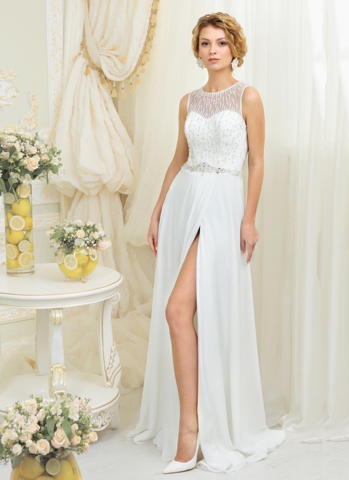Прямое свадебное платье с высоким разрезом на юбке и оригинальной вышивкой сверху.