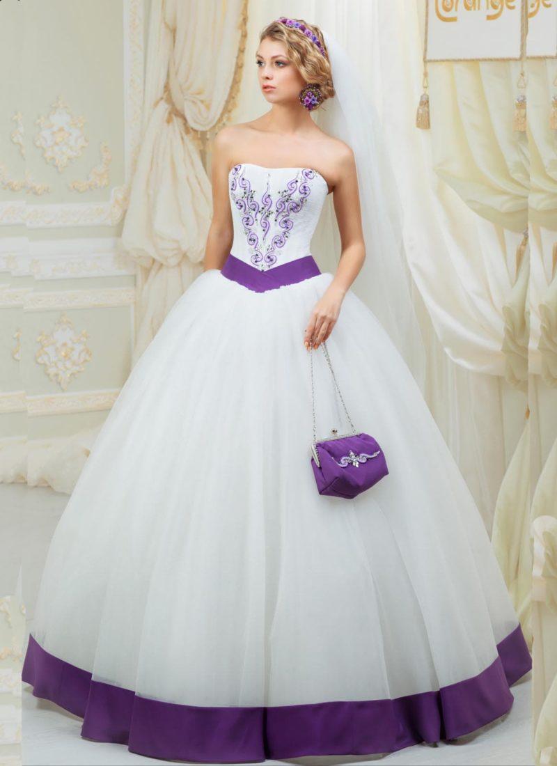 Стильное пышное свадебное платье с отделкой фиолетовым атласом и вышивкой того же цвета.