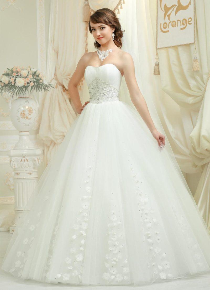 Открытое свадебное платье с пышной юбкой, украшенной аппликациями, и вышивкой на корсете.