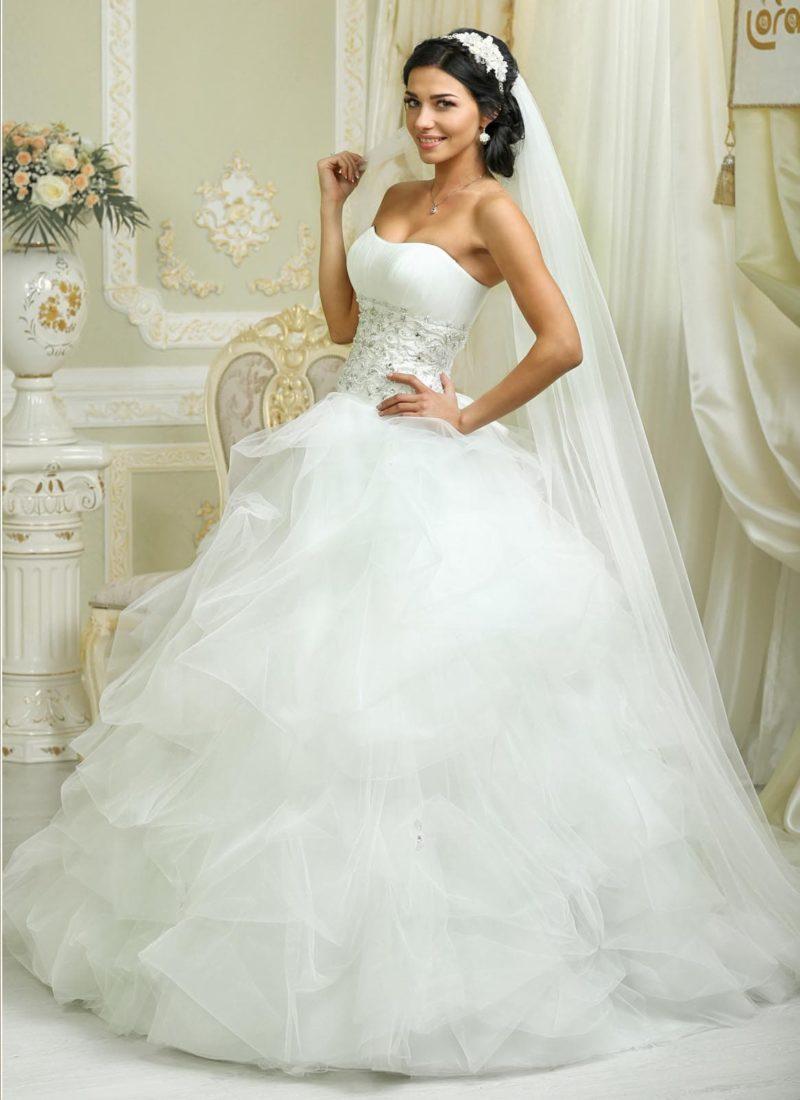 Романтичное свадебное платье с пышными оборками на юбке и чувственным корсетом.
