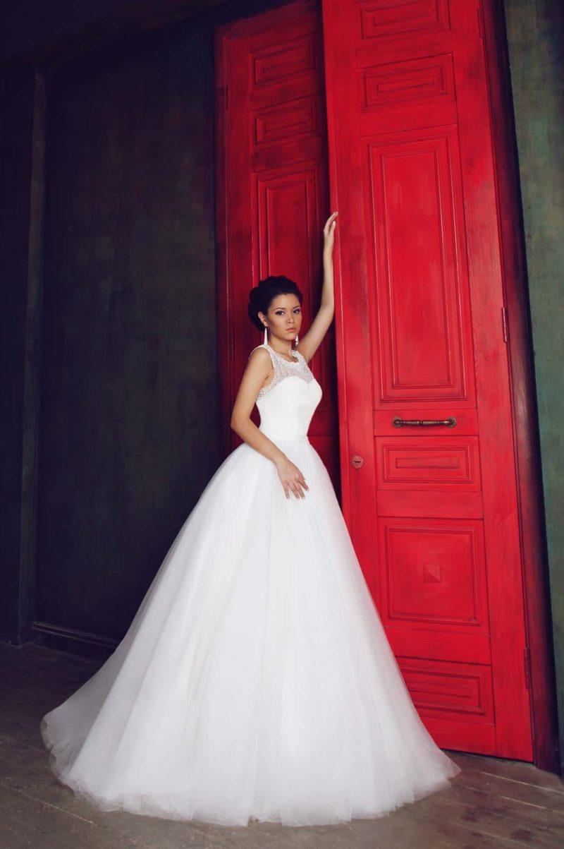 Пышное свадебное платье с закрытым лифом, отделанным тонкой кружевной тканью.
