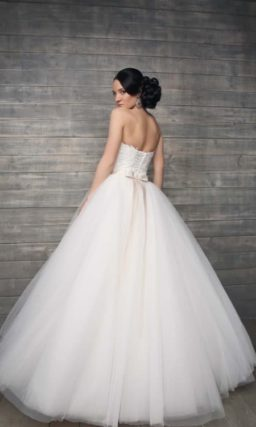 Пышное свадебное платье с открытым корсетом, покрытым плотным слоем кружевной ткани.
