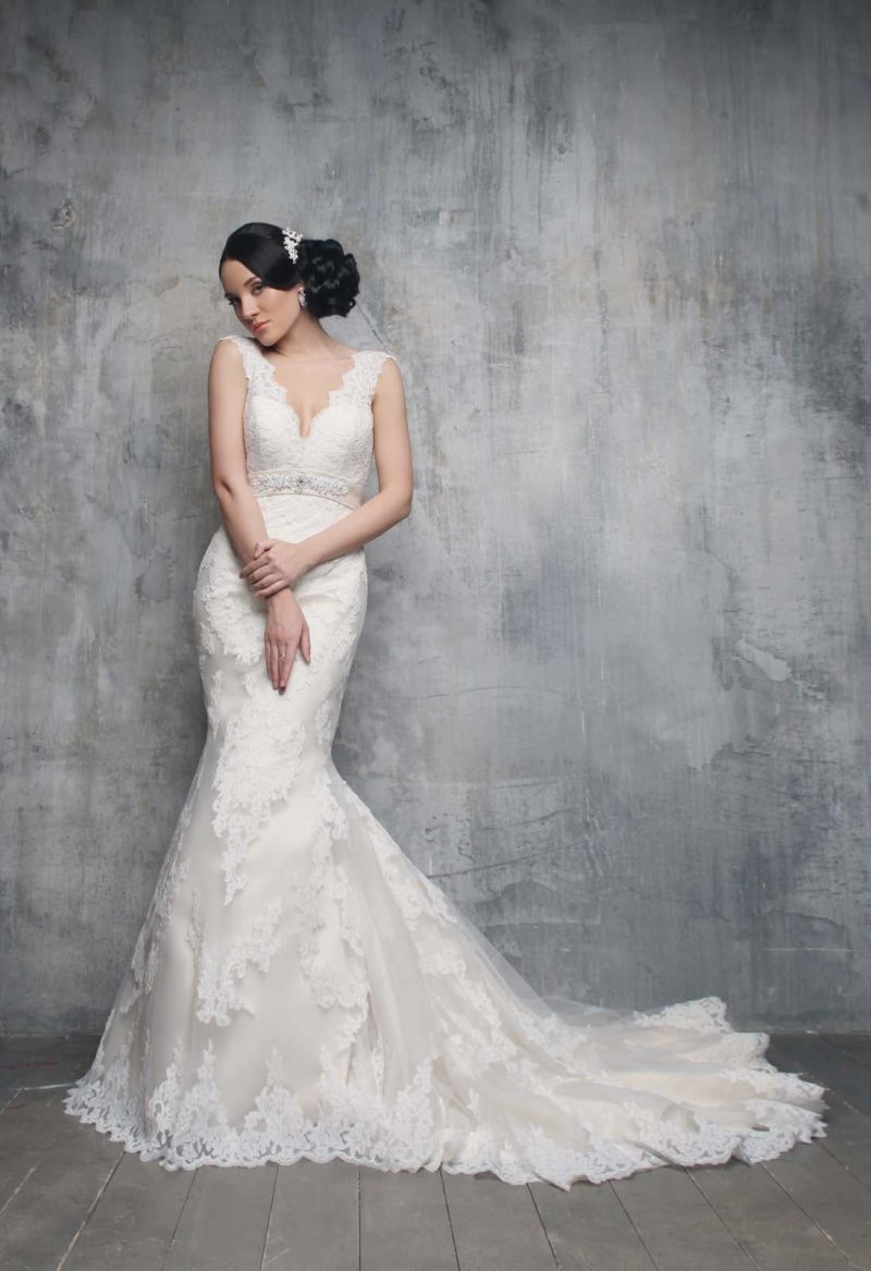 Кружевное свадебное платье с силуэтом «рыбка» и глубоким V-образным декольте.