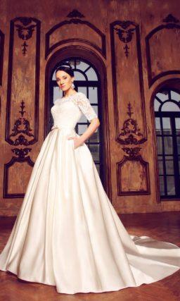 Атласное свадебное платье силуэта «принцесса» с кружевным лифом с длинными рукавами.