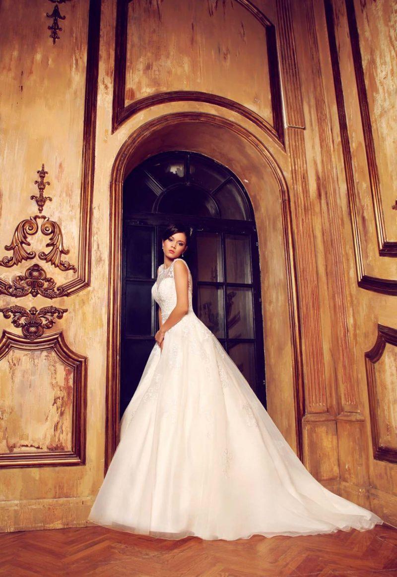 Пышное свадебное платье с закрытым кружевным лифом и узким бисерным поясом.