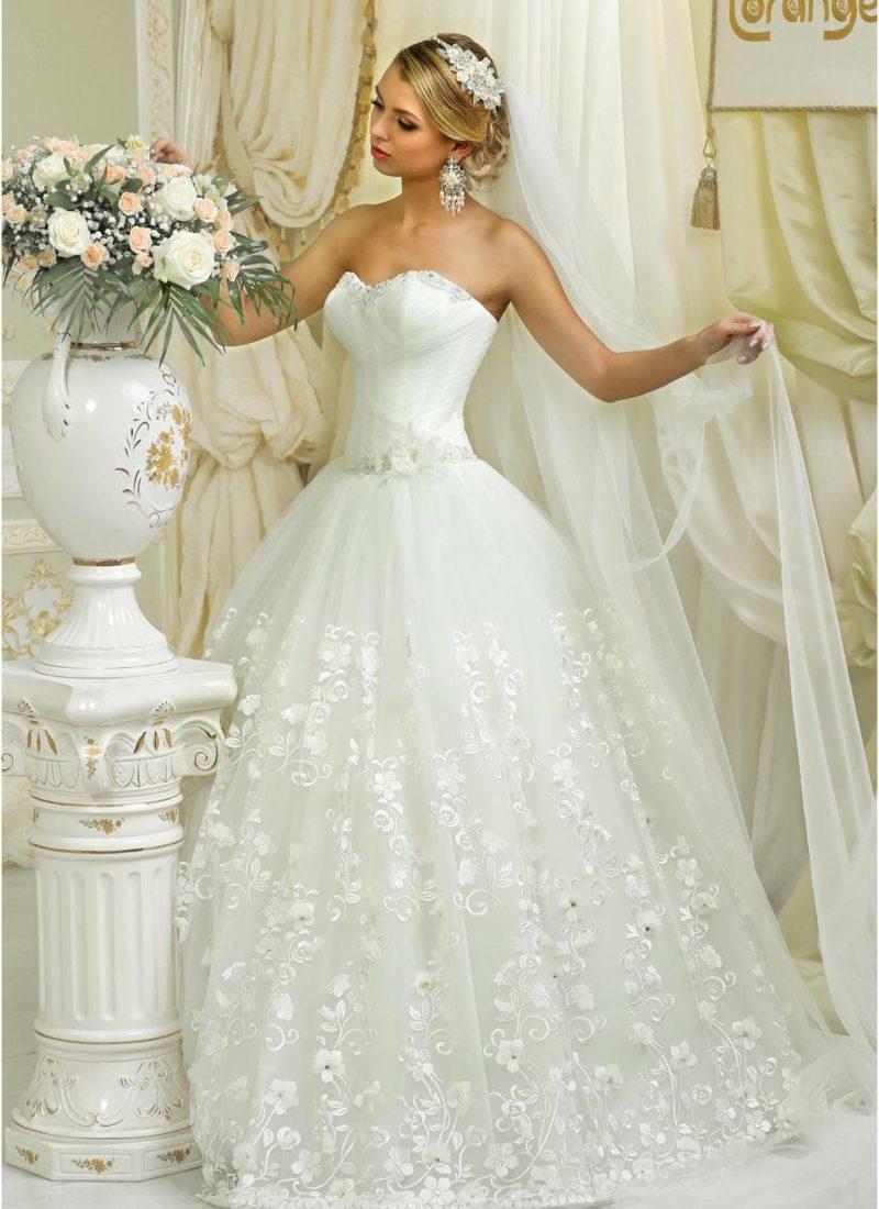 Открытое свадебное платье пышного силуэта с глянцевым цветочным узором на юбке.