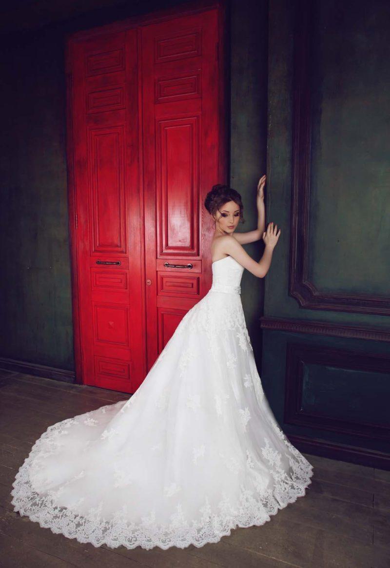 Открытое свадебное платье силуэта «принцесса» с юбкой, покрытой кружевными аппликациями.