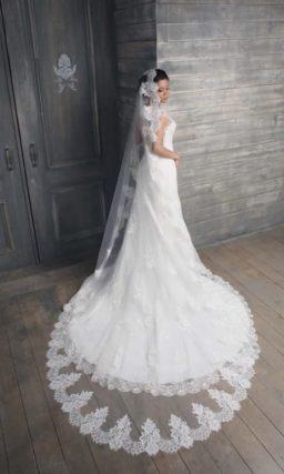 Закрытое свадебное платье силуэта «рыбка» с длинным полупрозрачным шлейфом.