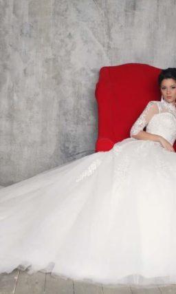 Закрытое свадебное платье силуэта «принцесса» с длинным шлейфом и рукавом в три четверти.