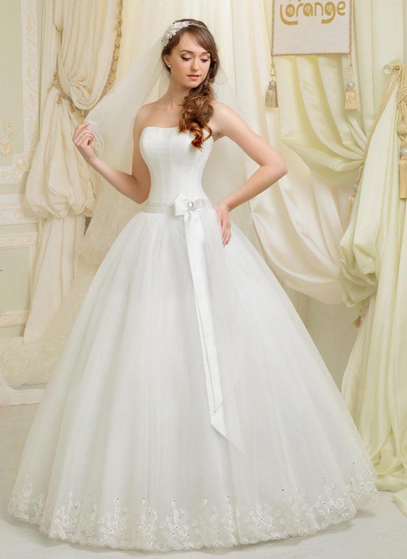 Открытое свадебное платье с широким атласным поясом и вышивкой по низу подола.