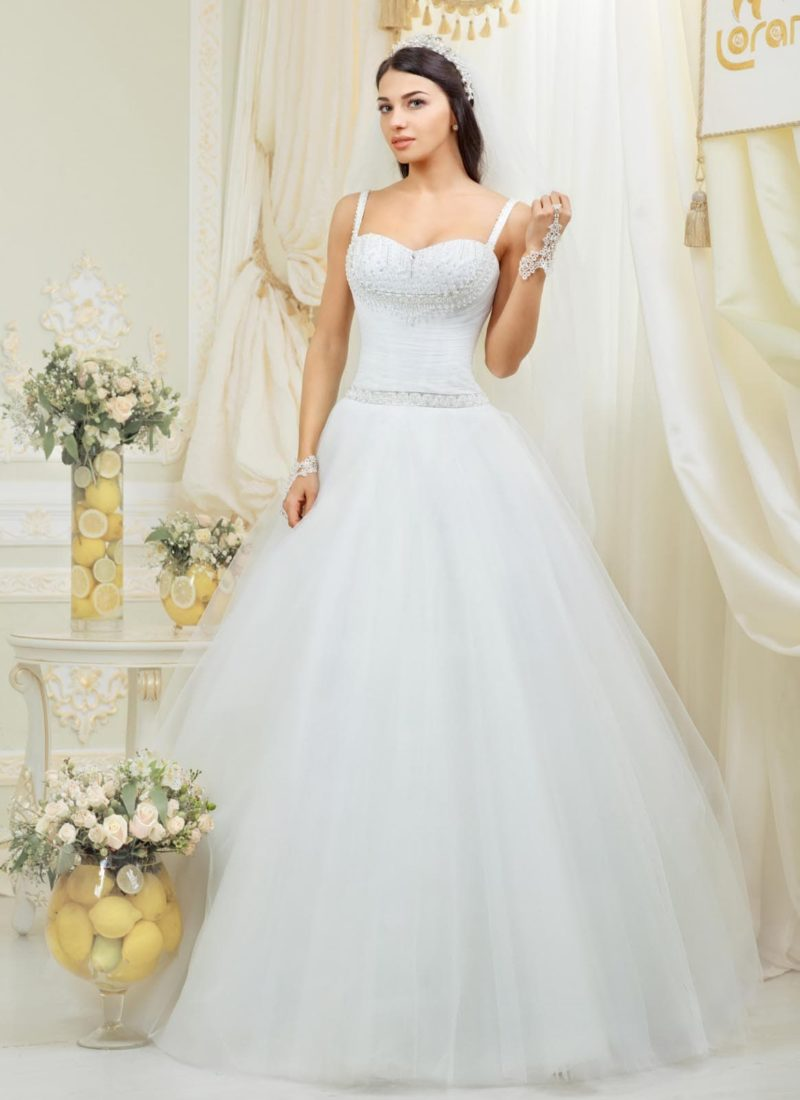 Открытое свадебное платье с узкими бретелями, вышивкой на лифе и пышной юбкой.