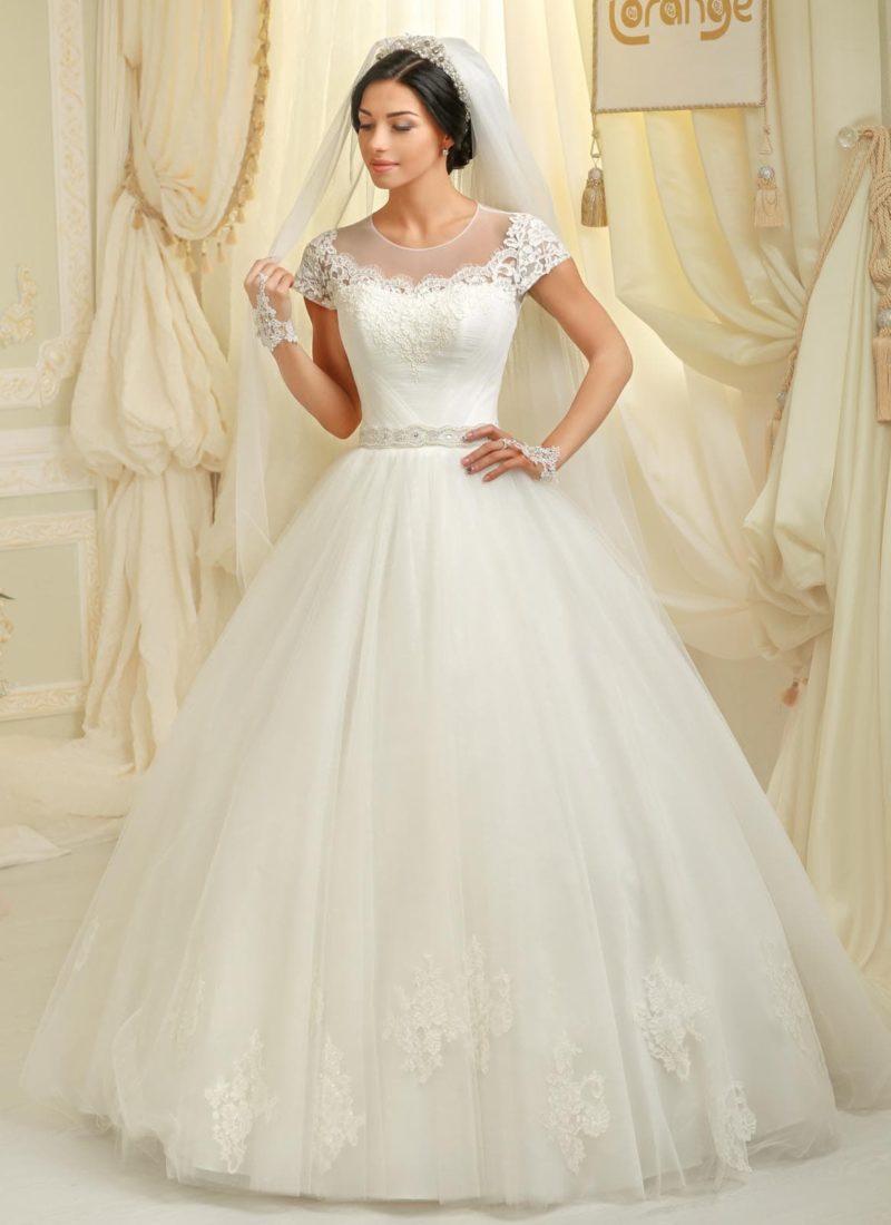 Пышное свадебное платье с аппликациями на юбке и закрытым лифом с коротким рукавом.