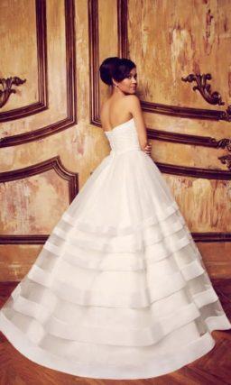 Пышное свадебное платье с открытым корсетом и горизонтальными полосами декора на юбке.