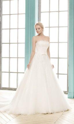 Открытое свадебное платье силуэта «принцесса» с кружевной отделкой под прозрачным верхом юбки.