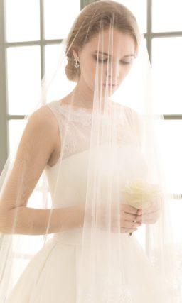 Свадебное платье силуэта «принцесса» с поясом на талии и кружевным декором лифа.
