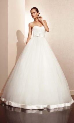 Свадебное платье с атласной отделкой юбки и широким поясом.
