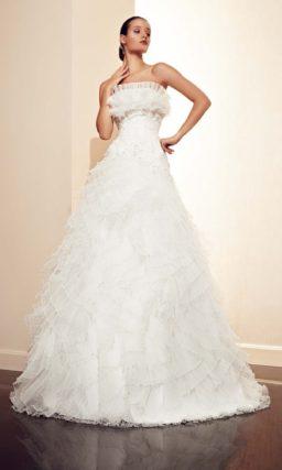 Свадебное платье силуэта «принцесса» с пышными оборками по лифу и подолу.