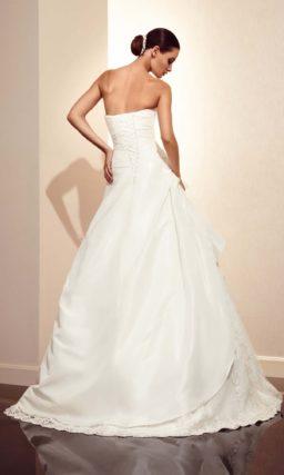Свадебное платье силуэта «принцесса» с открытым лифом и объемной отделкой.