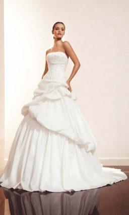 Свадебное платье с прямой линией декольте и пышной отделкой подола.