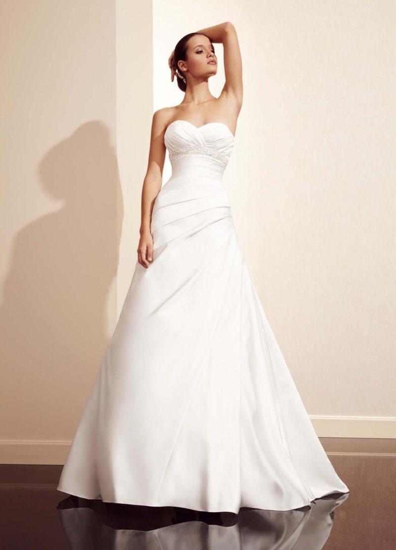 Свадебное платье из глянцевой ткани, с открытым лифом и драпировками.