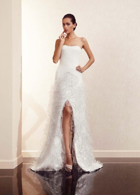 Прямое свадебное платье с открытым лифом и пышной полупрозрачной отделкой юбки.