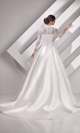 Закрытое свадебное платье с пышным силуэтом и длинными ажурными рукавами.