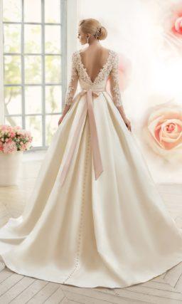 Свадебное платье силуэта «принцесса» с поясом из розового атласа и кружевными рукавами.