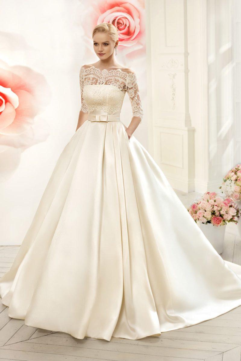 Атласное свадебное платье пышного силуэта с портретным декольте и широким поясом.