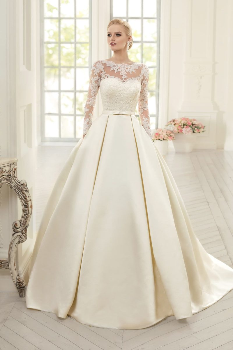 Пышное свадебное платье с юбкой из атласа и длинными кружевными рукавами.