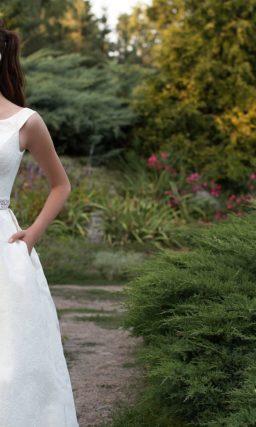 Свадебное платье из фактурной ткани с широкими бретелями и открытой спинкой.