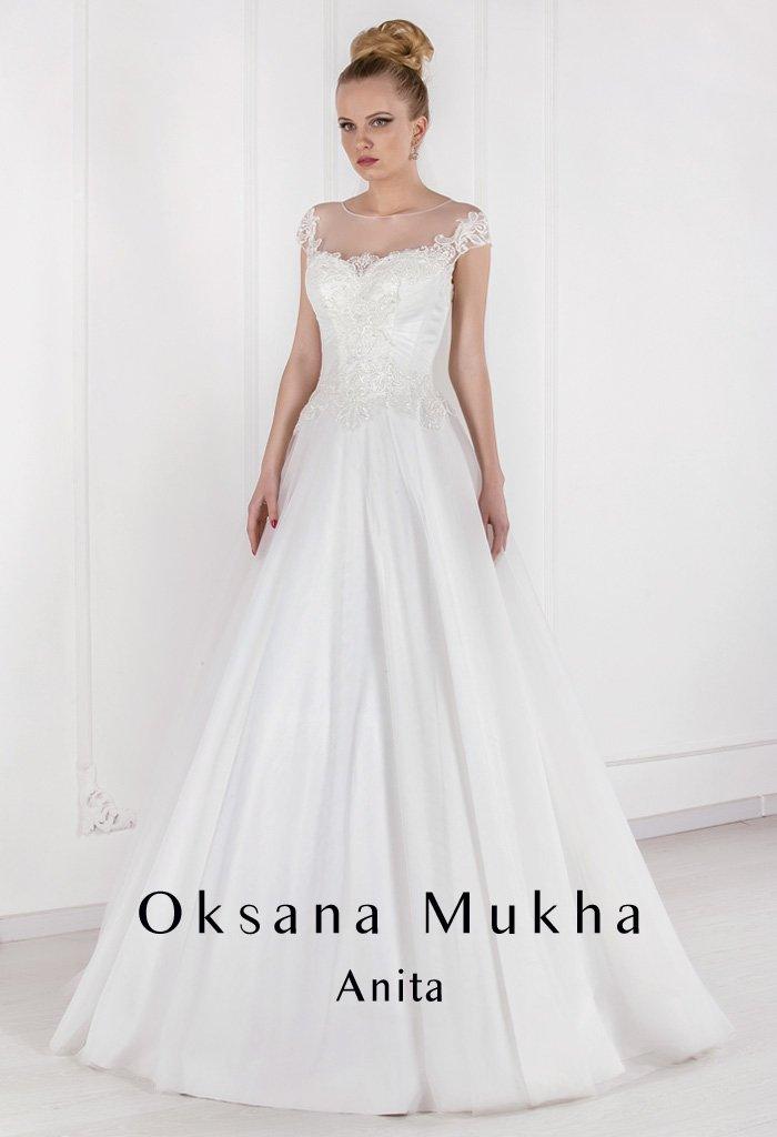 Атласное свадебное платье с вырезом на спинке, покрытым прозрачной тканью.