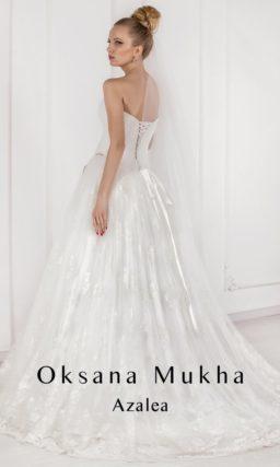 Открытое свадебное платье с пышной юбкой с декором глянцевым кружевом и драпировками на корсете.
