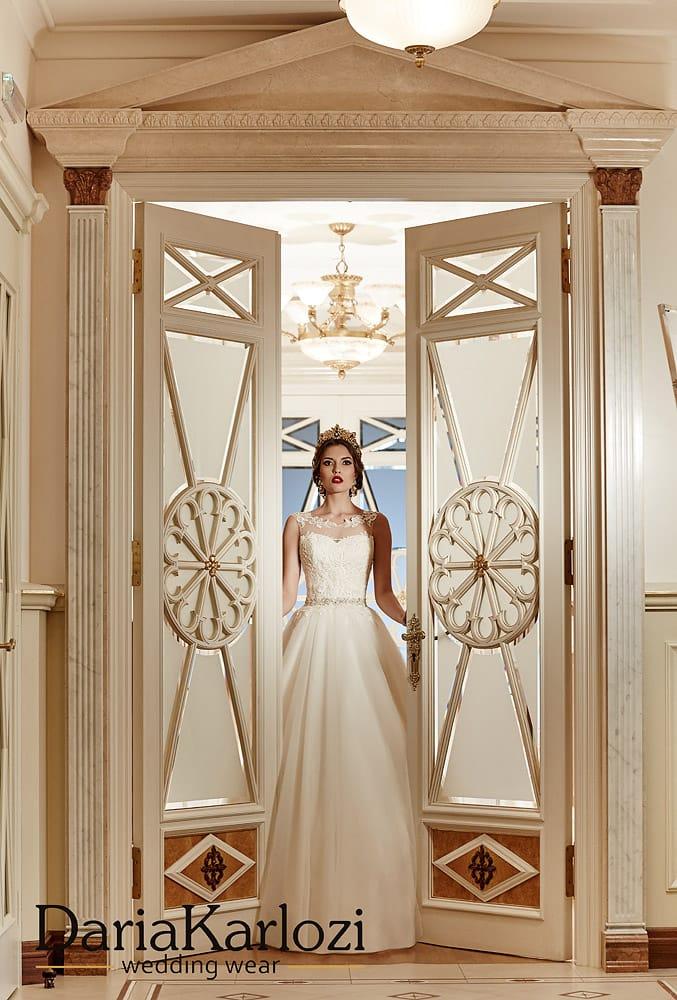 Пышное свадебное платье с полупрозрачной вставкой над открытым корсетом.