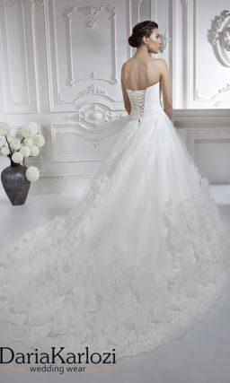 Открытое свадебное платье с кружевным лифом и объемной отделкой юбки.