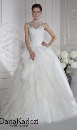 Пышное свадебное платье с закрытым лифом и покрытым оборками подолом.
