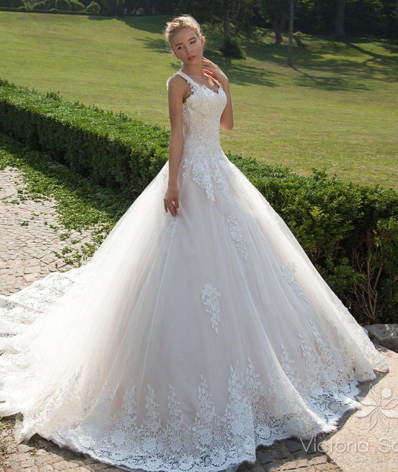 Пышное свадебное платье кремового оттенка с кружевным декором.