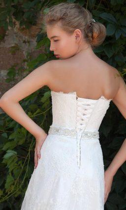 Прямое свадебное платье с открытым корсетом по всей длине оформлено кружевом.
