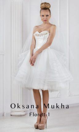 Короткое свадебное платье с пышной юбкой сложного кроя и корсетом, украшенным бутонами.