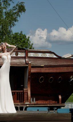 Свадебное платье с силуэтом «рыбка» и глубоким вырезом лифа, дополненным кружевом.