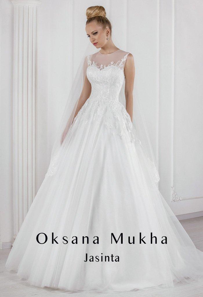 Свадебное платье А-силуэта с полупрозрачным оформлением верха, дополненным аппликациями.