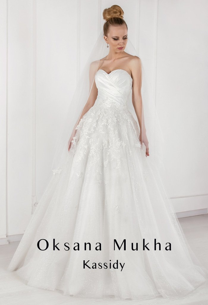 Нежное свадебное платье с силуэтом «принцесса», закрытым верхом и полупрозрачными рукавами.