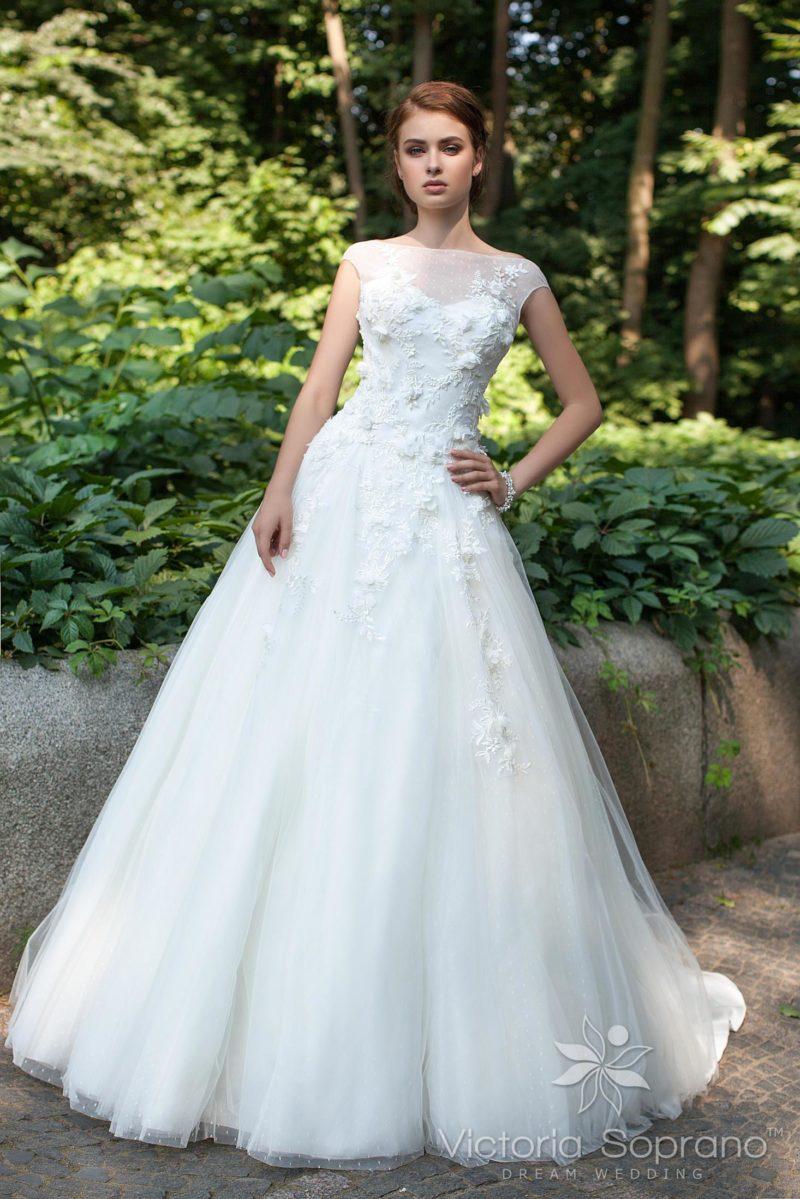 Закрытое свадебное платье с полупрозрачной вставкой и аппликациями.