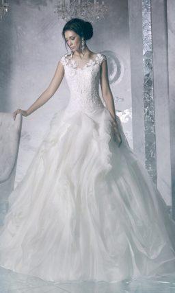 Пышное свадебное платье с закрытым лифом и юбкой, покрытой объемными складками ткани.
