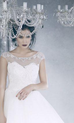 Закрытое свадебное платье с пышной юбкой, украшенной объемными оборками.