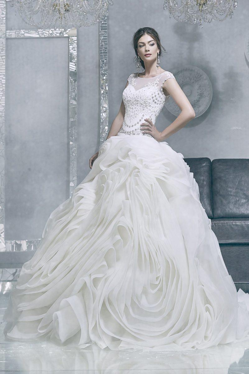 Свадебное платье с расшитым бисером верхом и пышной юбкой со множеством оборок.