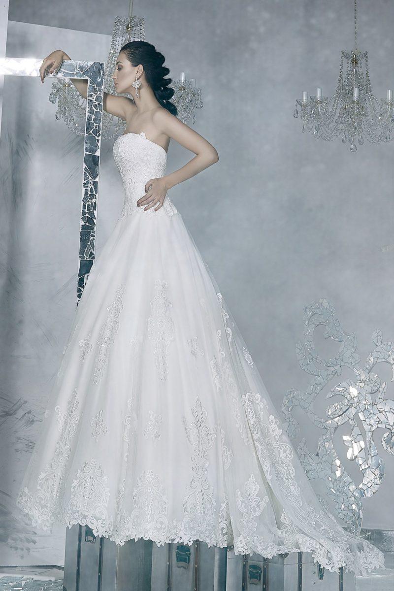 Свадебное платье с открытым лифом прямого кроя, украшенным кружевом.