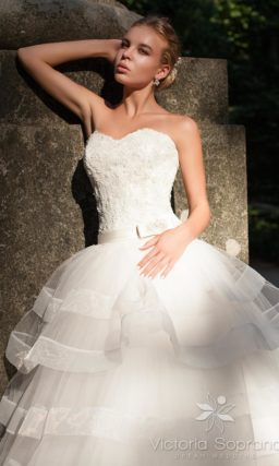 Пышное свадебное платье с открытым лифом и юбкой, покрытой множеством оборок.